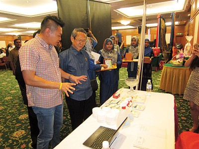 梁荣光(右)浏览展出绿色工艺产品的柜台,抱负责人邵建绅(左)的详细讲解。
