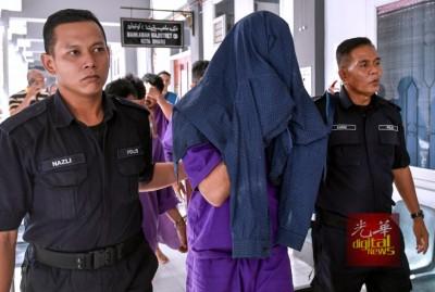 用衣服盖头的阿末沙费涉嫌拥毒,周三被控上法庭时不认罪,获准保外候审。