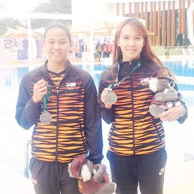 在个人赛夺冠的潘德蕾拉和队友梁敏仪(右)展示女双跳台赛银牌。