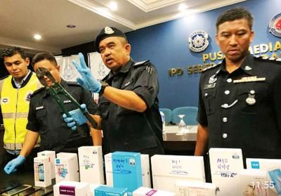 诺再尼(右2)向记者展示在突击行动中,被搜出的手机。