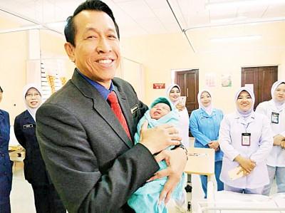 拿督诺希占被初生宝宝深深吸引,忍不住双手抱起宝宝。