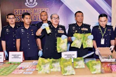 马兹南(着)展示已为混入毒品的虽溶包装饮料。