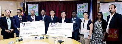拉古胡南达南(左4)移交救灾基金予林冠英(左5),由众议员及代表见证。
