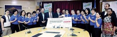 梁绣瑛(右9)移交救灾基金予林冠英(左9),由众议员及代表见证。
