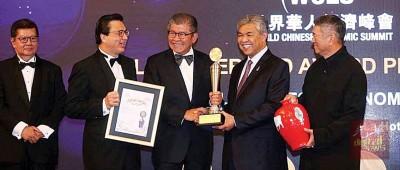 """副首相拿督斯里阿末扎希(右2)在峰会上,颁发""""世界华人终身成就奖""""予许廷忠(中),表扬他卓越非凡的成就。陪同的左起是丹斯里杨元庆、拿督斯里廖中莱和丹斯里李金友。"""