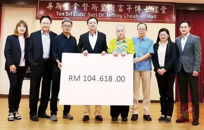 张润安(左4)移交捐款模拟支票 。潘琳沁(左起)、袁福扬、黄天才、赖观福、丘伟田、古卓瑜与李致宇。
