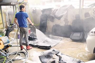 员工使用高压水将沾满泥浆的地毯清洗干净。