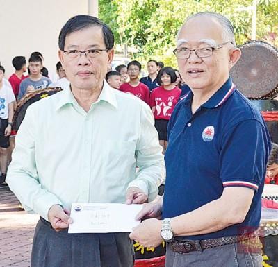 锺焕池(左)移交活动赞助基金予日新独中,由陈奇杰接领。