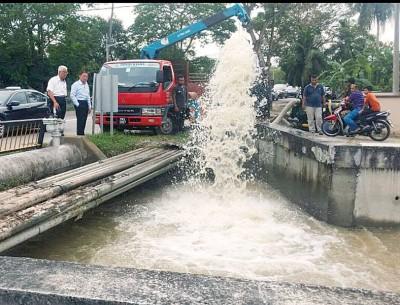 左起彭文宝与林峰成巡视双溪赖水利灌溉局进行水泵抽水行动。
