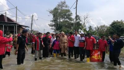 纳吉(左6)紧牵着罗斯玛(左5),小心翼翼涉水至祈祷室探访灾民。