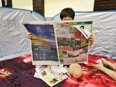 贪图为灾民张女士在读书《光日报》。