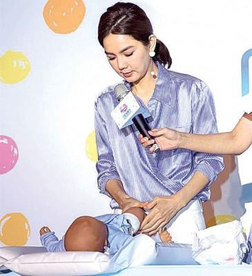 Ella在活动上挑战替假宝宝换尿布十分熟练。