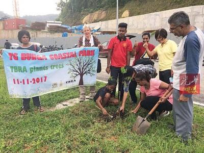 安娜斯(右2)与数名丹绒武雅居民协会成员,在发生土崩事故的丹绒武雅建筑工地对面空地,种下由槟岛市政厅所提供的树苗。