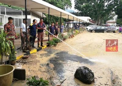 柔佛马华义务消防队汲取河水冲洗遍地泥泞的锺灵校地。\