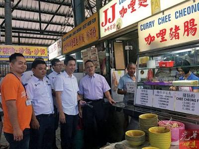 胡栋强(左3)在黄皓溗(左起)、陈政雄及黄忠荣的陪同下,前往峇央峇鲁小贩中心分派「微型贷款」及「转型贷款」申请表格给当地贩商。