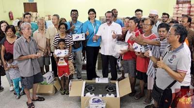佳日星(左6)于周六上午在大英义组屋的人民礼堂分派物资给水灾灾民。