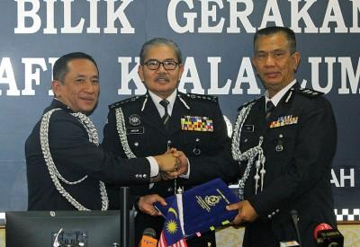 马兹南(中)周四见证纳兹里(左)移交吉隆坡交通调查与执法组主任的职权给祖基菲里。