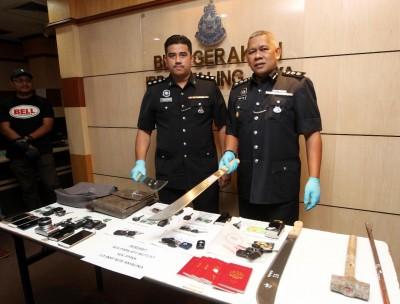 莫哈末扎尼(右)与立功警官出示匪徒的作案工具、失车车匙与一些遇劫财物。