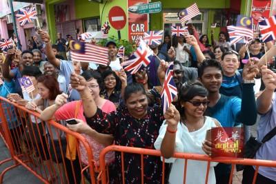 民众手持我国及英国国旗,头顶艳阳,夹道欢迎王储伉俪抵达。