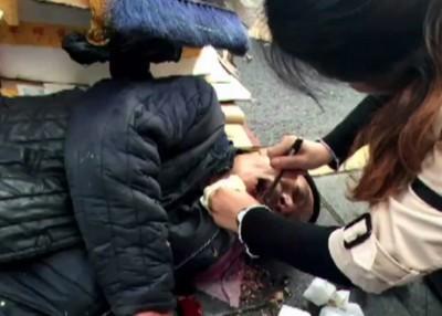 张瑾帮助老翁从其口中掏出食物残渣。