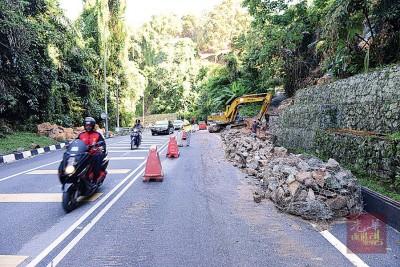工作人员正积极抢修遭土崩破坏的防崩墙。