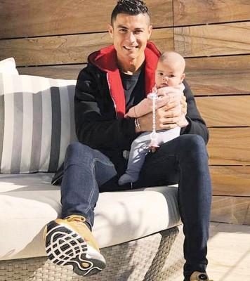 在社交网络上,C罗发了自己与大女儿伊娃的合影。C罗坐在沙发上,伊娃坐在他的左大腿上。还不到半岁的伊娃被剃了个光头,奶胖奶胖的脸颊透着可爱。