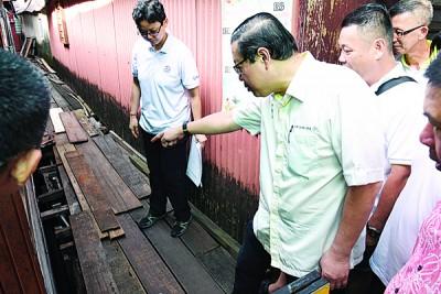 林冠英(右)每当洪敏芝当人口之伴随下巡视姓周桥被白蚁侵蚀的木桥梁。