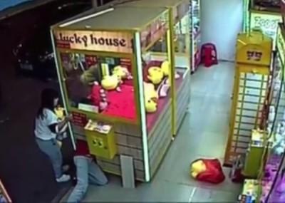 穿红衣的女子钻进夹娃娃机的取物口,偷取多只玩偶。