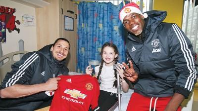 曼联球星伊布及博格巴于曼彻斯特皇家儿童医院为小球迷献上签署球衣。