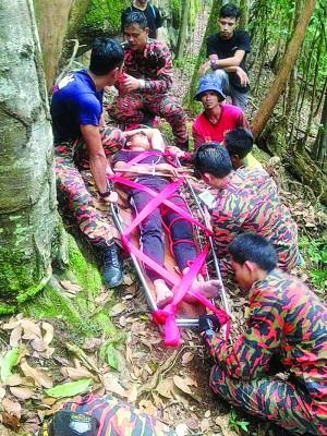 脱拯员合力将受伤青年抬下山。