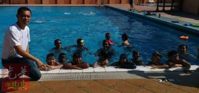 杨式丰也刚以游池里接受训练的残障少年打气。