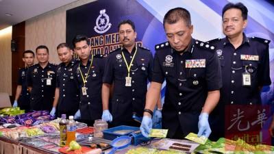 阿南(右2)周二在记者会,与立功警官出示搜到的各种毒品与包装工具。