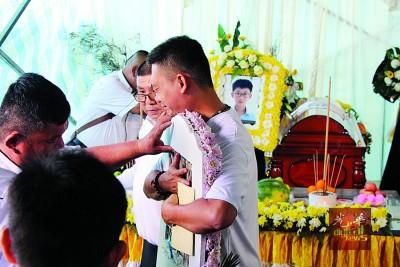 4名至亲举殡日当天,林瑞木拥抱至亲的相片,不舍地道别。