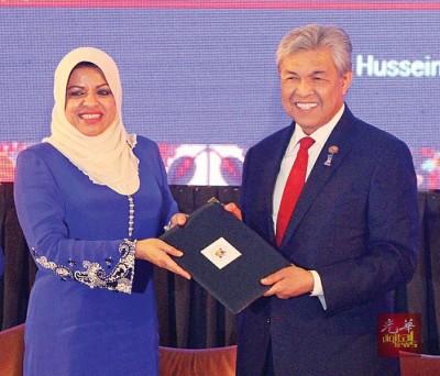 莎丽扎(左)向阿末扎希提呈国际女性政治论坛所达致的决定案。