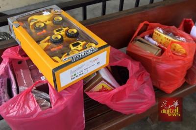 家属们为逝者准备身后事用品,包括为小死者添购重型车玩具。