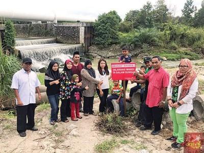 廖彩彤与赛奥曼及12岁溺毙孩童双亲及村民们一起到河边立告示牌,警惕小朋友切勿到河边嬉水。