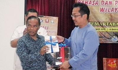 阿米鲁受(左)送纪念品给为南马区马来文学和语言大会主持开幕的拉查里。