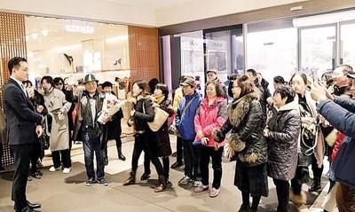 中华游客到首尔的一律里免税店购物,售货员准备花束、纪念迎接。