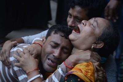 丧礼发生人踩人事件,死者家属抱头痛哭。(法新社照片)