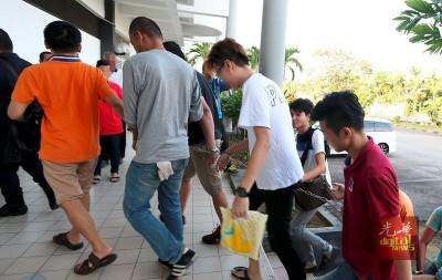 被告联同其他嫌犯在警员押送下抵达大山脚法庭。