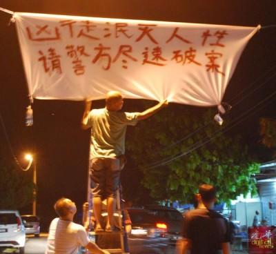 愤愤不平的柔府村民在王国安丧府前入口挂起布条。