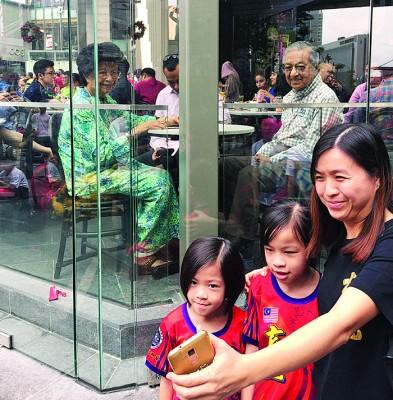 马哈迪(右)与茜蒂哈斯玛也在元旦来到柏威年购物商场享用早点,并与隔在玻璃窗外的民众合影。