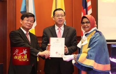 """林冠英(中)展示槟岛市政厅推展的""""2018目标""""计划书,左为曹观友及右为麦慕娜。"""