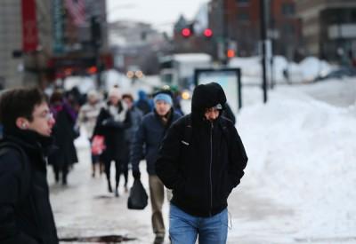 民众穿上厚厚的衣服避寒。(法新社照片)