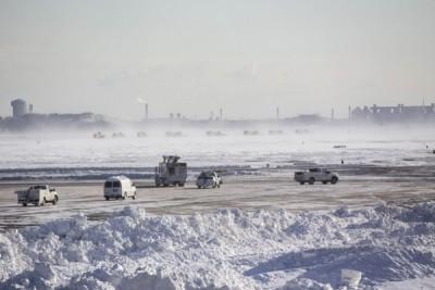 波士顿机场的工作人员忙于清理积雪。(法新社照片)