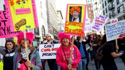 """多口戴上赫赫有名的粉红色针织""""小猫帽"""",暗指特朗普都以视频中吹嘘,可肆无忌惮抓女性下体。"""