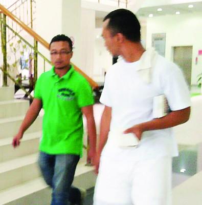 被告(右)当庭获释后,同朋友步离法庭。