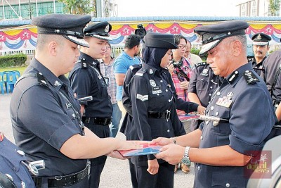 哈斯南(右)以月集会中宣告表扬状给下霹雳肃毒组池宜成警长。