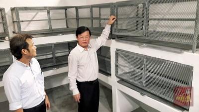 """曹观友(右)与尤端祥巡视""""疾病控制与兽医中心""""内猫笼。"""