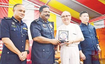 居民代表(右起)洪明宝、邱庆河赠送纪念品予达威甘,左为威中警区主任聂罗斯。